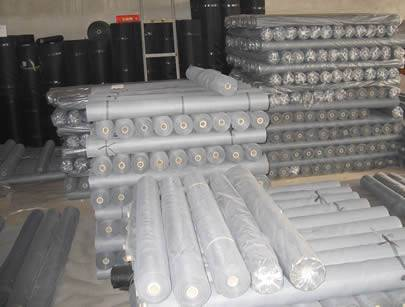 Black, grey and white fiberglass screen rolls in our warehouse