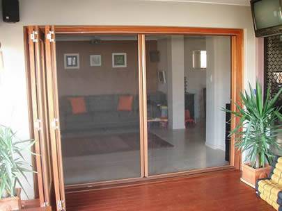 Two sliding doors in a house are made of galvanized insect screen.