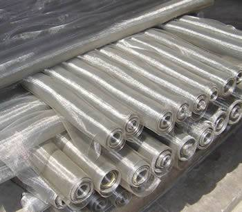 Several rolls of stainless steel insect screen are on the ground.